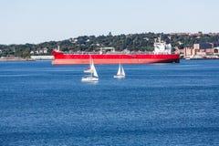 Witte Zeilboten door Oranje Vrachtschip Stock Afbeelding