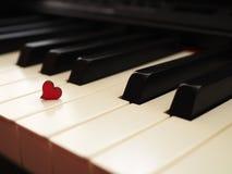Witte zwarte piano met rood hart royalty-vrije stock fotografie