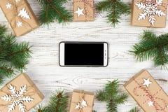 Witte zwarte smartphone met het geïsoleerde scherm, boven houten bureau met Kerstmisdecoratie Hoogste mening stock fotografie