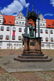 Wittenberg Luther statue. Wittenberg market place with Luther statue holding the new testament. In the back the former townhall, now a museum and exhibition stock image