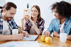 Witty inventive guy writing something in his notebook. Playing games. Attractive mysterious cool men intriguing his friends while playing with them guessing a Stock Images