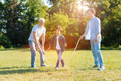 Witty nice men using the rope for jumping. Creative use. Witty wonderful handsome family members having an active weekend in the park and playing with his family Royalty Free Stock Image