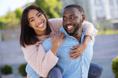 Witty string guy giving his girl a ride. Active day. Lively creative romantic men having fun outside with his girl as she jumping on his back and hugging him Royalty Free Stock Image