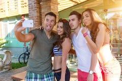 Witze über junge Leute, während sie selfiet tun Stockfoto