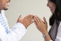 Forgiving and apologizing each other. eid mubarak. Wive shake and kiss her husband`s hand during muslim eid mubarak celebration. forgiving and apologizing each royalty free stock images