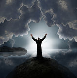 Wizard. Man holding arms up in praise against sunset royalty free stock image