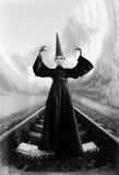 Wizard. In black cloak and dunce hat standing on rails. Black and white image Stock Photography