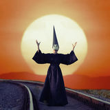 Wizard. In black cloak and dunce hat standing on rails at sunset Royalty Free Stock Image