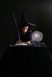 Wizard boy writing with a feather Stock Images