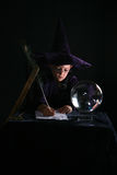 Wizard boy writing a spell Royalty Free Stock Photos