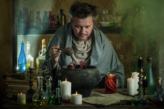 Wizard brews  potion. The wizard brews a potion Stock Image