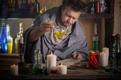 Wizard brews a potion. Indoor Stock Photography