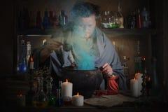 Wizard brews a potion. Indoor Stock Photos