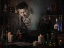 Wizard brews a potion. Indoor Royalty Free Stock Images