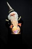 Wizard casting a spell. Wizard with hat and crystal ball staring at viewer and casting a spell Royalty Free Stock Photography