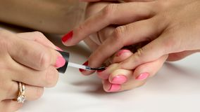 Wizard causes on the nail of client a binder. Close up. Manicure causes the top coat to the nail of the little finger, specialist establishes the nail polish on stock video