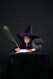Wizard child with peacock feather pen Royalty Free Stock Image
