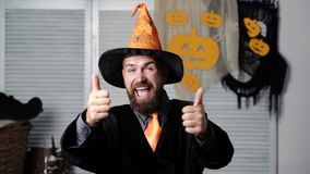Wizard on Halloween. Funny wizard holds thumbs up. Thumbs up. Happy Halloween. Halloween costume and decoration, magic. Spell and sorcery concept. Bearded man stock video