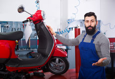 Wizard has finished work on the repair of motorcycles. The young wizard has finished work on the repair of motorcycles in his workshop Royalty Free Stock Photography