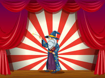A wizard holding a wand in the middle of the stage Stock Photos