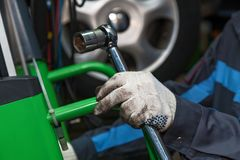 Disk brake repair in the car. The wizard holds the adjustable wrench. The man is repairing the disc brake machine, close-up. Disk brake repair in the car stock photo