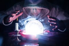 Wizard with hood and lights smoke magic crystal ball. Wizard with white hood and lights smoke magic crystal ball on desk with candle in candlestick and old books royalty free stock images