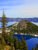 Wizard Island in Crater Lake. Wizard Island in the crystal clear blue waters of Crater Lake in Crater Lake National Park in Oregon Royalty Free Stock Images