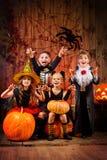 Wizard kids. Cheerful children in halloween costumes celebrating halloween in a wooden barn with pumpkins. Halloween concept stock photo