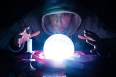 Wizard with magic glowing orb and hand holding above a glass of light stock images