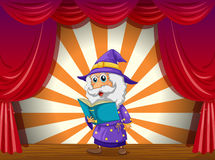 A wizard reading in the middle of the stage Stock Photo