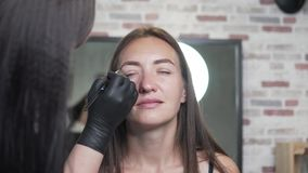 The wizard shapes the brows of the client. A woman puts on a black eyebrow brush. Satisfied salon visitor sits in an armchair and enjoys the process stock video footage
