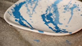 The wizard splashes blue paint on a white plate. On the table with burlap. Creative workshop stock video footage