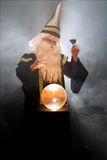 Wizard toasting with wine. Wizard invites viewer to have some wine Stock Photography