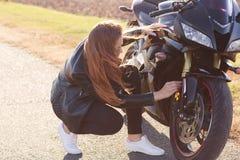 Wizerunek żeński rowerzysta jest ubranym czerni ubrania i biali sneakers, naprawiają motocykl, stojaki na drodze, rozwiązują prob zdjęcie royalty free