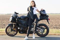 Wizerunek atrakcyjna kobieta jest ubranym białą t koszula, czarny spodniowy i biali trenery, siedzą na motorrbike, utrzymanie ręk zdjęcie royalty free