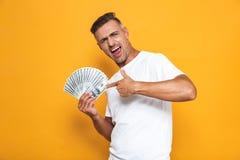 Wizerunek bogaty facet 30s w białej koszulce uśmiecha się wiązkę pieniądze i trzyma obraz royalty free