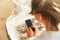 Wizerunek caucasian dziewczyna 20s jest ubranym słuchawki używać telefon komórkowego, podczas gdy chodzący nadmorski obraz royalty free