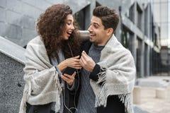 Wizerunek caucasian para mężczyzna, kobieta jest ubranym słuchawki i, słucha muzyka wpólnie podczas gdy stojący nad szarym budynk obrazy stock