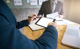 Wizerunek dwa młodego biznesmena używa touchpad dyskutuje documen obraz stock