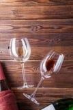 Wizerunek dwa wino butelki wina szkła na i brown, drewnianym tle, Fotografia Royalty Free