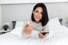 Wizerunek europejska kobieta 30s jest ubranym słuchawki areszt przy sądzie telefon, podczas gdy kłamający w łóżku w jaskrawym pok obrazy royalty free