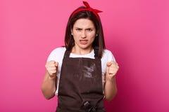 Wizerunek gniewna kobieta gniósł jej ręki w pięści, dama jest ubranym tshirt, fartuch, włosiany zespół, pozy przeciw różowej stud zdjęcie stock