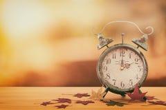 Wizerunek jesień czasu zmiana Spada z powrotem pojęcie Suszy liście i rocznika budzika na nieociosanym drewnianym stole zdjęcie royalty free