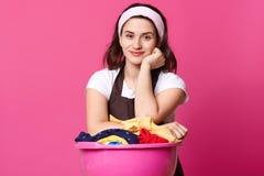 Wizerunek kobieta stoi blisko ogromnego różowego basenu z świeżym odziewa, koc, ręczniki i inny dom tkanina, konowie myje, obrazy stock