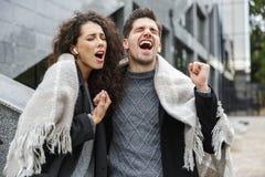 Wizerunek kochający para mężczyzna, kobieta jest ubranym słuchawki i, słucha muzyka wpólnie podczas gdy stojący nad szarym budynk obrazy royalty free