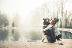 Wizerunek młoda dziewczyna z jej psim, alaskim malamute, plenerowym zdjęcie stock