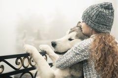Wizerunek młoda dziewczyna z jej psim, alaskim malamute, plenerowym fotografia stock