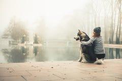 Wizerunek młoda dziewczyna z jej psim, alaskim malamute, plenerowym zdjęcia stock