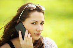 Wizerunek młoda piękna dziewczyna w miasto parku mówi telefonem komórkowym Zdjęcia Royalty Free