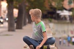 Wizerunek młody blond chłopiec obsiadania krzyż iść na piechotę patrzejący ulicę za on z miękką ostrością uliczne i drzewne linie Zdjęcia Stock